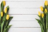 """Постер, картина, фотообои """"вид сверху красивый желтый тюльпан цветы белые деревянные поверхности"""""""