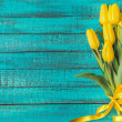 Beautiful yellow tulips with ribbon on turquoise w...