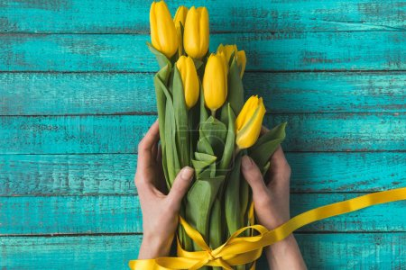 cropped shot of person holding beautiful yellow tulips with ribbon