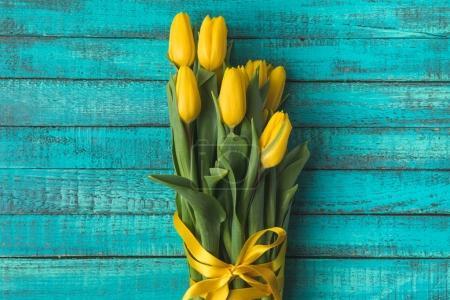 Foto de Vista superior de hermosas flores de tulipán amarillo con cinta en la superficie de madera turquesa - Imagen libre de derechos
