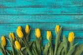 """Постер, картина, фотообои """"вид сверху красивый желтый тюльпан цветы на бирюзовый деревянные поверхности"""""""