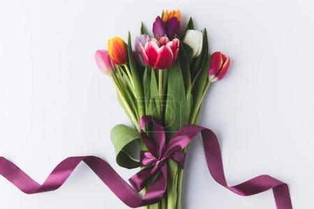 Photo for Beautiful colorful tulips with purple ribbon isolated on grey - Royalty Free Image