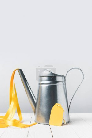close-up view of shiny watering pot with yellow ribbon and blank tag on grey
