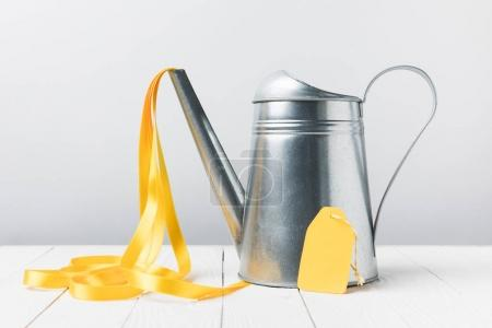 close-up view of shiny watering can with yellow ribbon and blank label on grey
