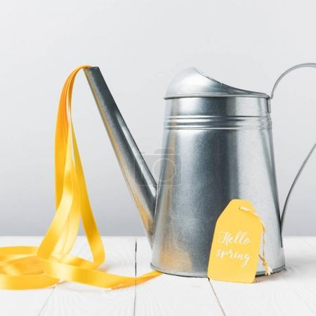 close-up view of shiny watering can with yellow ribbon and hello april lettering on tag