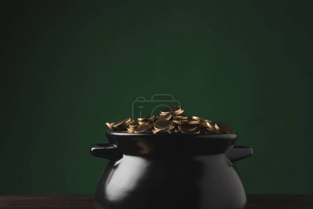 pot of golden coins on wooden table on green, st patricks day concept