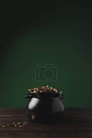 black pot of golden coins on wooden table on green, st patricks day concept