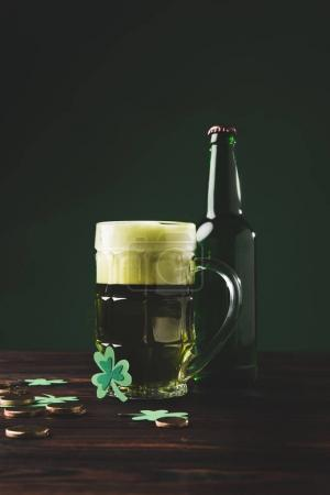 glass of beer with shamrock and golden coins on table, st patricks day concept