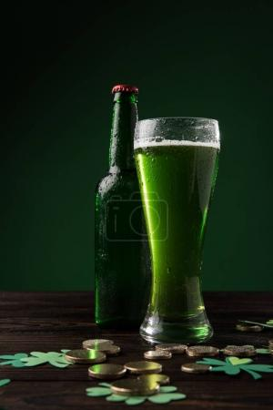 glass of green beer and bottle on table, st patricks day concept
