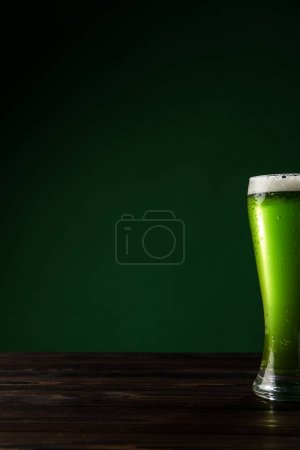 glass of green beer on wooden table, st patricks day concept
