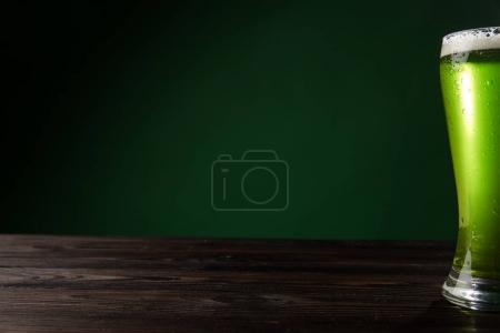 Photo for Glass of green beer with foam on wooden table, st patricks day concept - Royalty Free Image