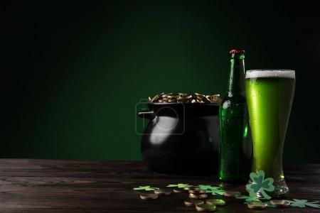 pot with golden coins and green beer on table, st patricks day concept