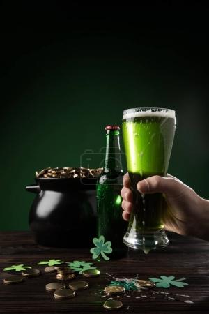 cropped image of man holding glass of green beer with pot of coins on table, st patricks day concept
