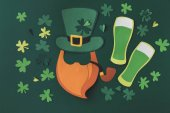 top view of paper decoration of smoking leprechaun with green beer for st patricks day isolated on green