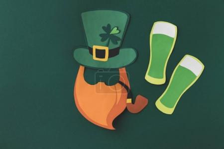 top view of paper decoration of smoking leprechaun and beer for st patricks day isolated on green