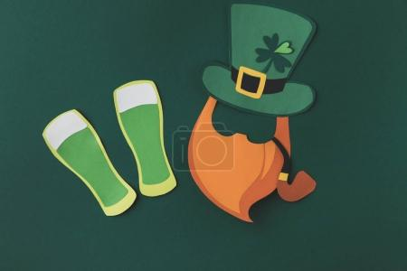 top view of paper decoration of man with smoking pipe for st patricks day isolated on green