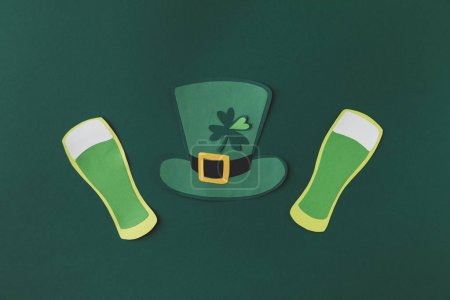 top view of paper decoration of green hat and beer for st patricks day isolated on green