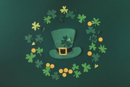top view of paper decoration of green hat and shamrock for st patricks day isolated on green