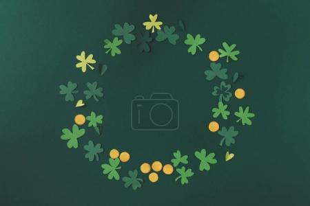 top view of paper decoration of coins and shamrock for st patricks day isolated on green