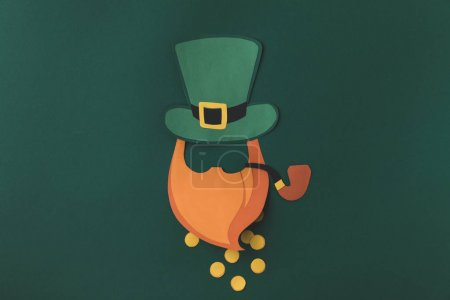 top view of paper decoration of leprechaun in green hat with coins for st patricks day isolated on green