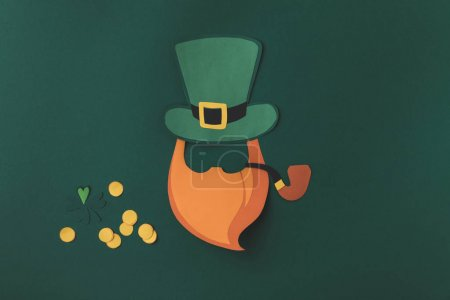 top view of paper decoration of leprechaun with smoking pipe for st patricks day isolated on green