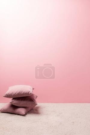 Photo pour Oreillers sur le tapis devant le mur rose - image libre de droit
