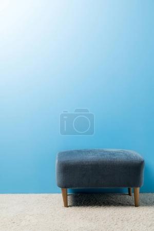 Doux hassock debout sur le tapis devant le mur bleu