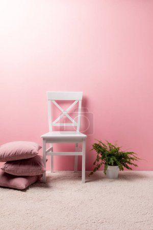 Photo for Chair with pillows and fern pot in front of pink wall - Royalty Free Image