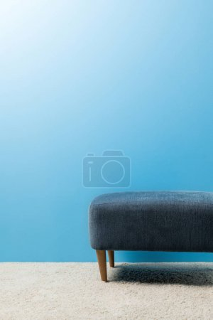 pouf standing on carpet in front of blue wall