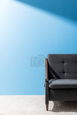 comfy grey couch in front of blue wall