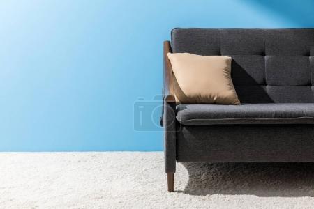 Photo pour Coussin allongé sur un canapé confortable en face de mur bleu - image libre de droit