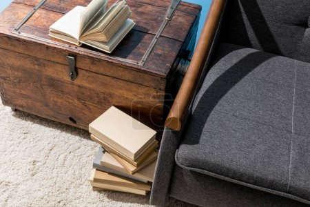 old chest used as bed table with stack of books