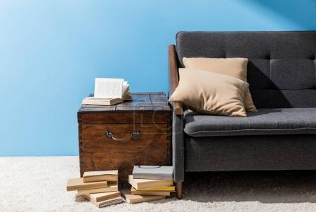 wooden chest with books near couch in front of blue wall