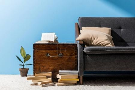 ancient wooden chest with books near couch in front of blue wall