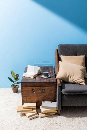 old wooden chest with cup of coffee and books near couch in front of blue wall