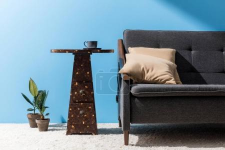 Couchtisch mit Tasse neben Couch vor blauer Wand