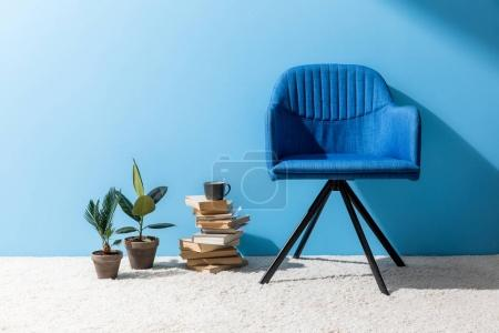 Photo for Cozy chair with books and ficus pots in front of blue wall - Royalty Free Image