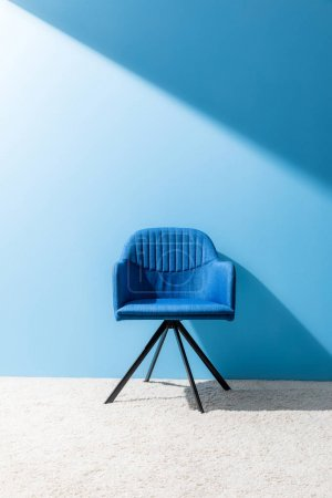 Photo for Comfy blue chair in front of blue wall - Royalty Free Image