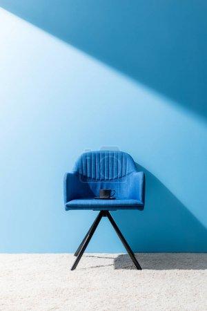 Photo pour Tasse de délicieux café sur la chaise devant le mur bleu - image libre de droit