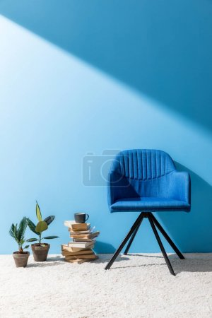 armchair with books and ficus pots in front of blue wall