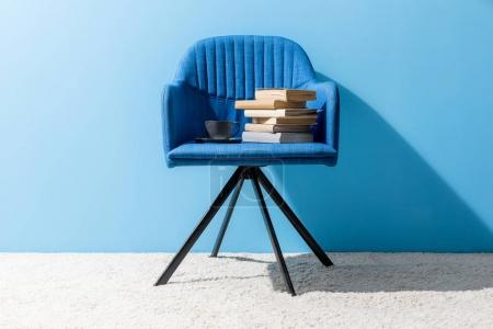 Photo for Cup of coffee and books on chair in front of blue wall - Royalty Free Image