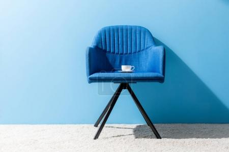 cup of coffee on chair in front of blue wall