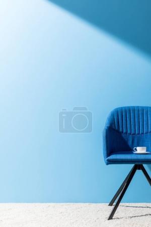 Photo pour Fauteuil bleu avec tasse de café devant le mur bleu - image libre de droit
