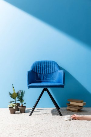 Photo for Comfy blue armchair with person holding cup of coffee on floor in front of blue wall - Royalty Free Image