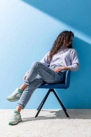 attractive young woman sitting in chair in front of blue wall