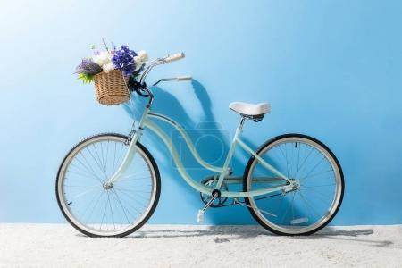 Photo for Side view of bicycle with flowers in basket in front of blue wall - Royalty Free Image
