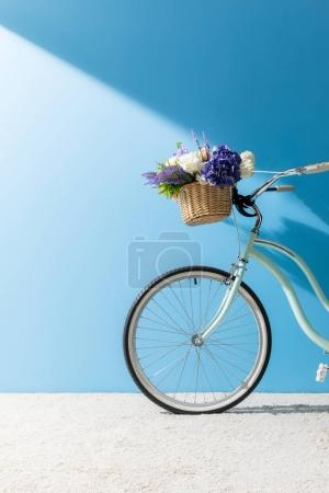 bicycle with flowers in basket standing on carpet in front of blue wall