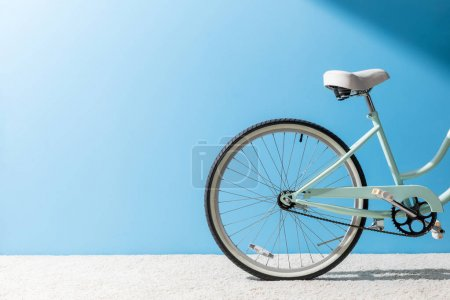 Photo for Back wheel of bicycle standing on carpet in front of blue wall - Royalty Free Image