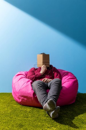 man reading book in bean bag in front of blue wall