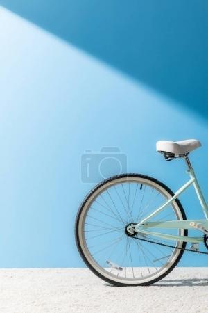 Photo pour Roue arrière du vélo devant le mur bleu - image libre de droit